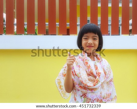 Cute little girl showing thumbs up on blurred background - stock photo