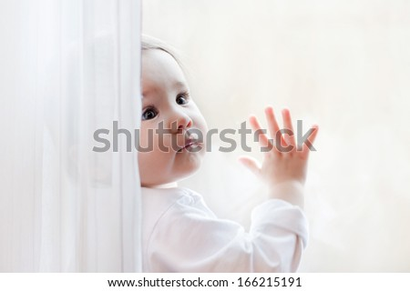 Cute little girl sits at window portrait. - stock photo