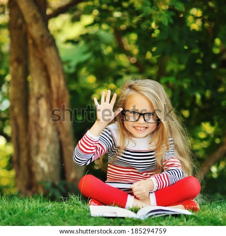 Cute little girl sits in a park. Reading book and hand gesture with 5 fingers - stock photo