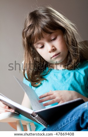 Cute little girl sitting and reading