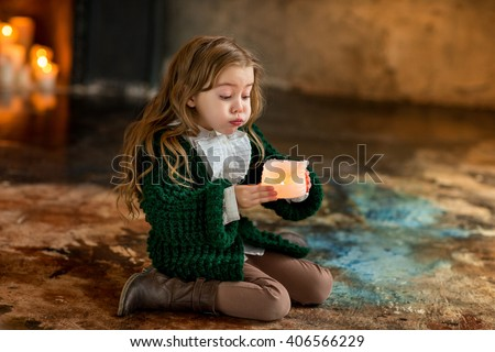 cute little girl sitting by the fire floor and blow out the candles