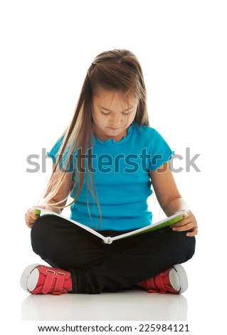 Cute little girl sitting cross legged and learning - stock photo