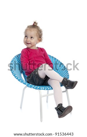 cute little girl sitting in a round blue chair. isolated on white background