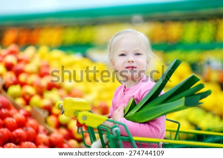Cute little girl sitting in a shopping cart holding a leek in a food store - stock photo