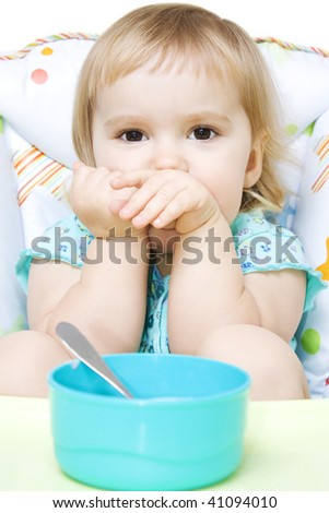 Cute little girl sitting in baby chair and don't want to eat