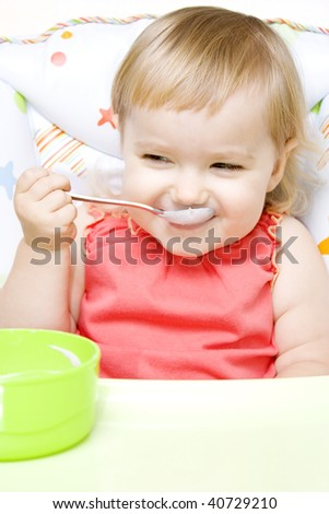 Cute little girl sitting in baby chair and eating with spoon 16-22 months