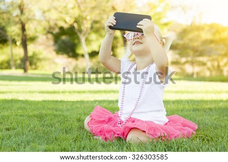 Cute Little Girl Sitting In Grass Taking Selfie With Cell Phone. - stock photo