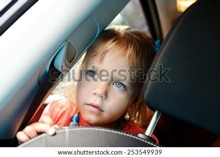 cute little girl sitting in the car - stock photo