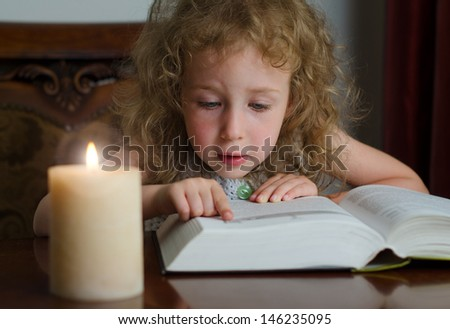 Cute little girl sitting in the dark with burning candle and reading a book