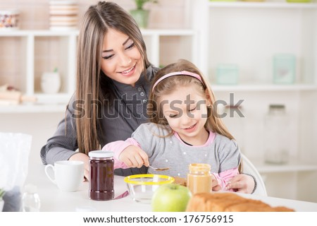 Cute little girl sitting in the mother lap and smearing peanut butter on bread. - stock photo