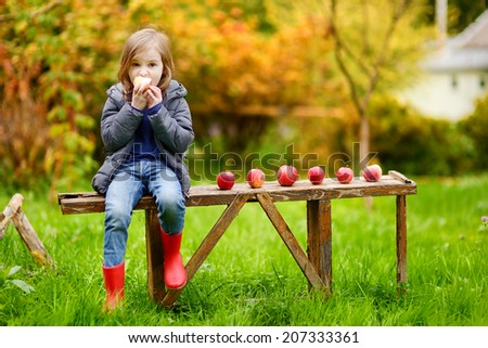 Cute little girl sitting on a wooden bench on autumn day - stock photo