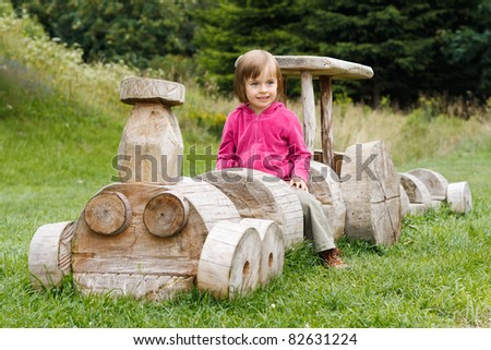 Cute little girl sitting on a wooden train - stock photo