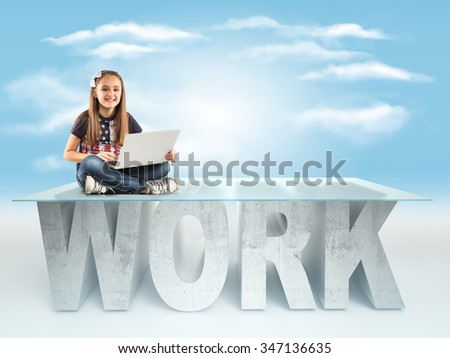 Cute little girl sitting on a WORK table design, and holding a laptop
