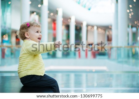 Cute little girl sitting on bench in huge mall - stock photo