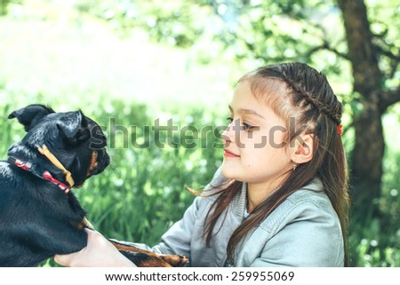 Cute little girl sitting on green grass and playing with her funny dog - stock photo