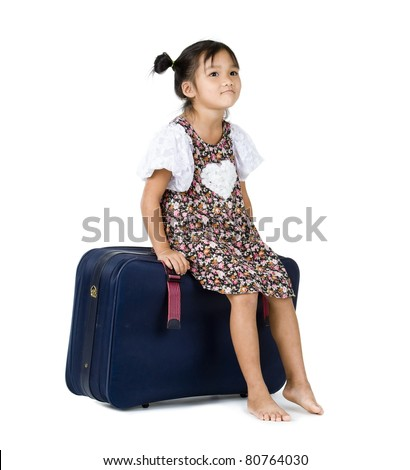 cute little girl sitting on her suitcase, isolated on white background - stock photo