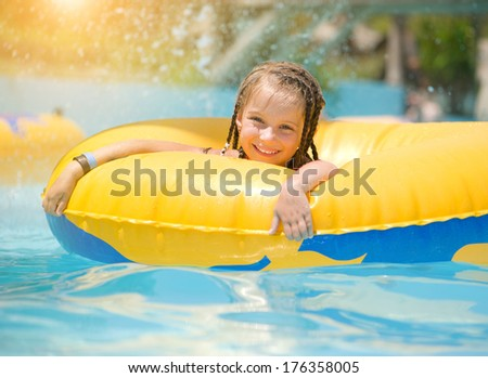 Cute little girl  sitting on inflatable ring in swimming pool. - stock photo