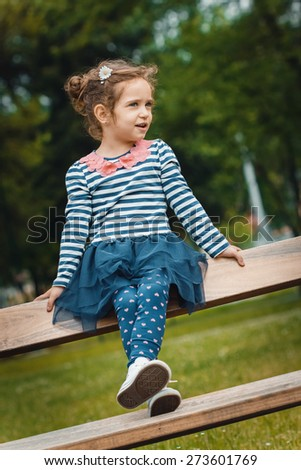 Cute little girl sitting on the bench in a park. Outdoors - stock photo