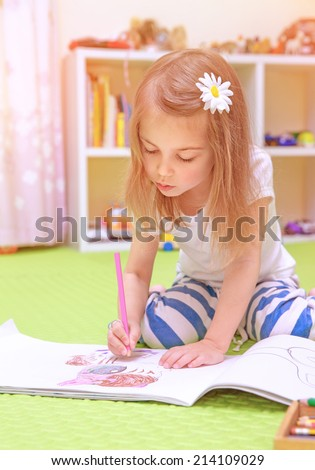 Cute little girl sitting on the floor and drawing picture to the album, having fun at home, happy childhood, having art talent concept - stock photo
