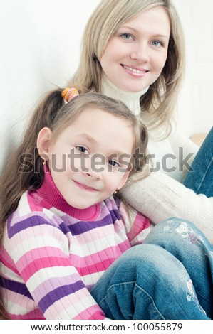 Cute little girl sitting on the floor at home with her mother