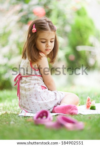 Cute little girl sitting on the grass, looking pensive.