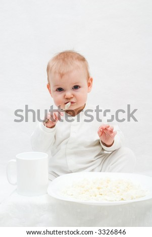 cute little girl sitting on white blanket with spoon in her hands. There are white plate with curd and white cup in front of her.