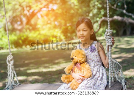 Cute little girl sitting swings , teddy bear sitting with her,little girl pointed to the tree.