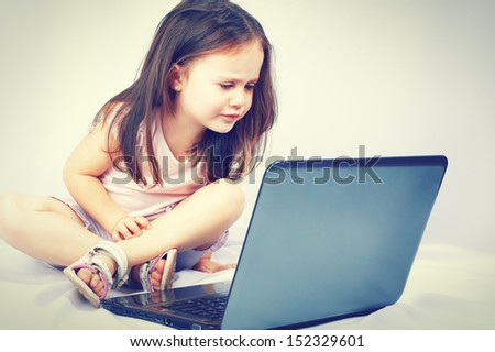 Cute little girl sitting with a laptop - stock photo