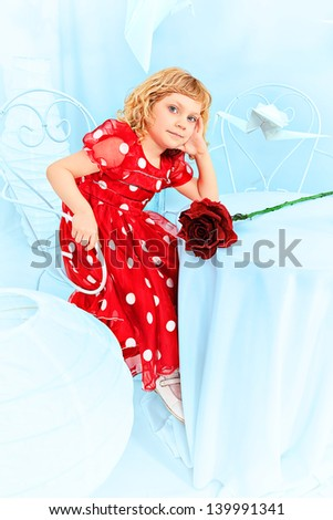 Cute little girl sitting with a red rose surrounded with paper birds. - stock photo