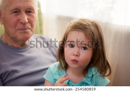 Cute little girl sitting with her grandfather  - stock photo