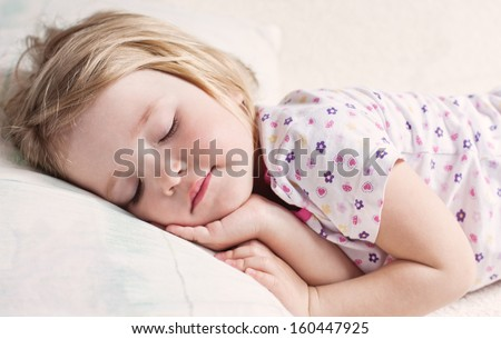 cute little girl sleeping on a bed in her pajamas - stock photo