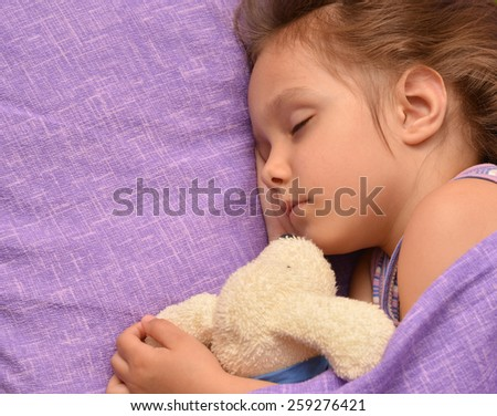 Cute little girl sleeping with a toy in her bed - stock photo