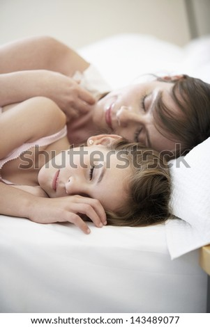 Cute little girl sleeping with mother in bed