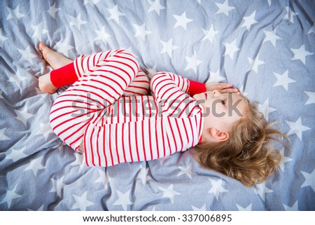 Cute little girl sleeps in striped pajamas in bed