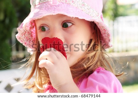 Cute little girl smelling a red rose