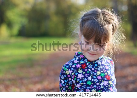 Cute little girl smiles and looks away in sunny green park, shallow dof, close up - stock photo