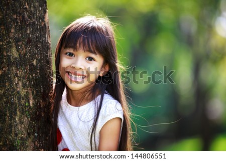 Cute little girl smiling in a park close up