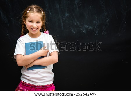 cute little girl smiling on black school board background with a blue book in hand - stock photo