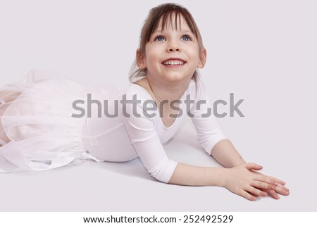 Cute little girl smiling over light grey background - stock photo
