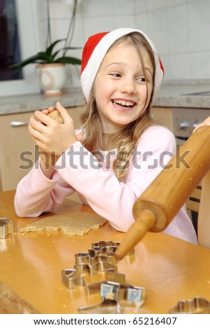 Cute little girl smiling while christmas baking - stock photo