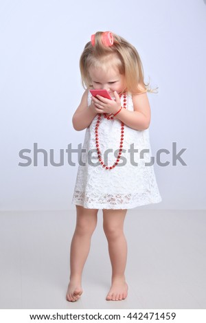Cute little girl smiling while looking in the mirror. Standing barefoot on a white background in studio - stock photo