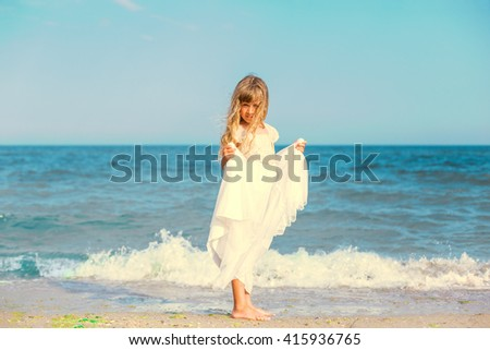 Cute little girl standing at ocean beach - stock photo