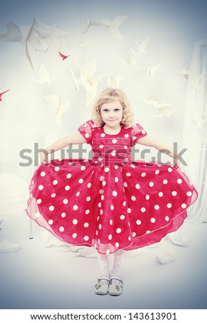 Cute little girl standing in a white room surrounded with paper birds. - stock photo