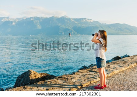 Cute little girl standing next to beautiful lake on sunset and looking in binoculars - stock photo