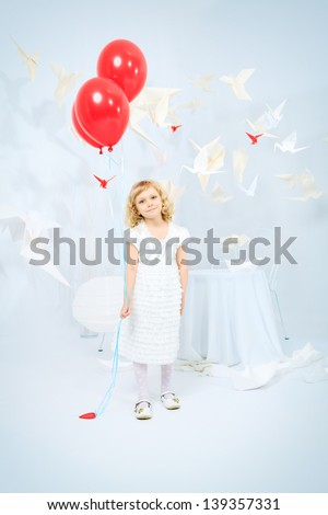 Cute little girl standing with red balloons in a white room surrounded with paper birds. - stock photo