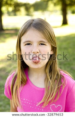 Cute little girl sticking out her tongue - stock photo