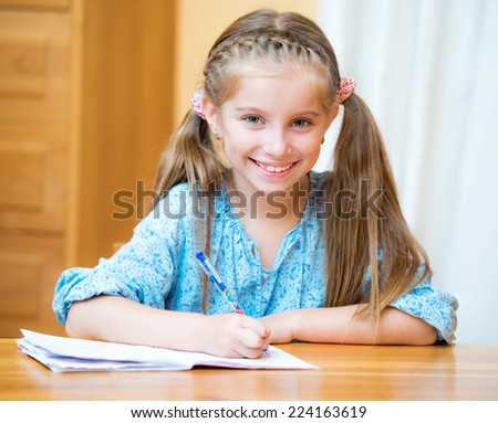 Cute little girl studying at home and smiling - stock photo
