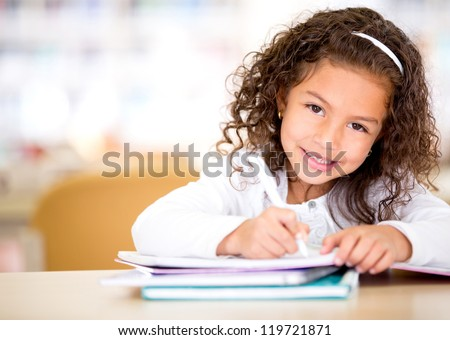 Cute little girl studying at the library and smiling - stock photo
