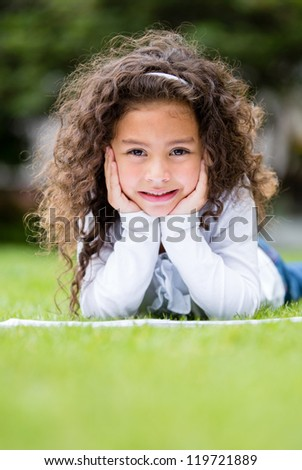 Cute little girl studying outdoors looking very happy - stock photo