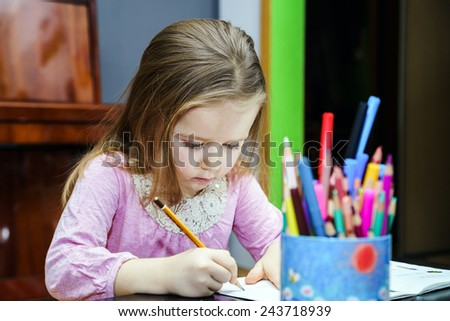 Cute little girl studying to speaking and writing letters at home lesson with her mother